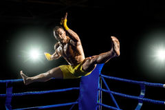 Thai boxer on boxing ring, jump and kicking Stock Image