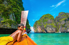 Thai boy on colorfull longtail boat in Thailand. THAILAND, PHI PHI ISLANDS - NOVEMBER 1, 2014: Thai boy on colorfull longtail boat with amazing view of Maya Bay Royalty Free Stock Images