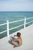 Thai boy fishing. Thailand, young Thai boy fishing on a pier in Rayong stock image