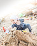 Thai  boy palying on  pile of sand with toy and plastic fork, sp Royalty Free Stock Image