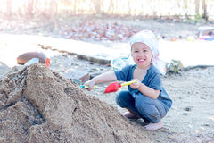 Thai  boy palying on  pile of sand with toy and plastic fork, sp Royalty Free Stock Photos