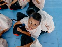 Thai boy with PE class school uniform sitting and closing his eyes at the blue floor of school. Hua Hin, Thailand September
