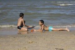 Thai boy play in the sand at the beach Stock Photos