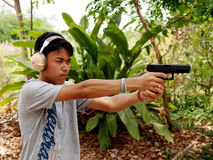 Thai boy shooting pistols Royalty Free Stock Photo