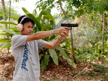Thai boy shooting pistols Stock Photo