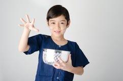 Thai boy splashing water by using hand  from bowl Royalty Free Stock Image