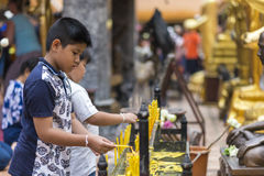 Thai boys light up a candle in temple. Thai young boys light up a candle in a temple, Chiang Mai, Thailand July 2016 Stock Photography
