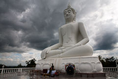 Thai budda. Whight budda in thailand with storm clouds rolling in Royalty Free Stock Photo