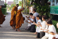 Thai Buddhist give food offerings to Buddhist monk Royalty Free Stock Image