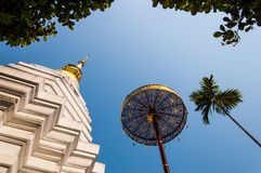 Thai Buddhist pagoda & golden umbrella. Thai pagoda, golden umbrella & palm tree against blue sky at Buddhist temple in northern Thailand Stock Photo