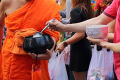 Thai buddhist put food to a monk`s alms bowl in Songkran festival Day.  Royalty Free Stock Images