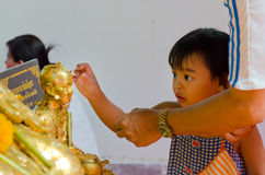 Thai child is learning to be a Buddhist. Wat Maitongsen Temple, Bangkok / 7 March 2012 is a Makha Bucha day. A father is teaching his little daughter to stick a Stock Image