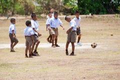 Thai children play football. PHITSANULOK, THAILAND - MAY 16, 2016: Thai children play football after lesson at Huay hoen School Stock Image