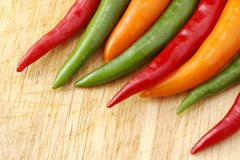 Thai Chillies. Red, orange and green Thai chillies on a wooden chopping board Royalty Free Stock Image