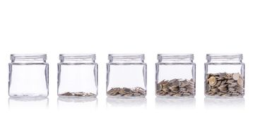 Thai coin (baht) in clear glass jar with different level from le Stock Photography