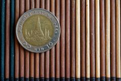 Thai coin denomination is 10 baht lie on wooden bamboo table, good for background or postcard. One Thai coin lie on wooden bamboo table, Denomination is ten baht stock photography