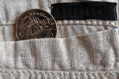 Thai coin with a denomination of 5 baht in the pocket of linen pants with black stripe for label. Thai coin with a denomination of five baht in the pocket of Stock Image