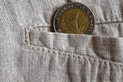 Thai coin with a denomination of ten baht in the pocket of worn linen pants. Thai coin with a denomination of 10 baht in the pocket of worn flax pants Royalty Free Stock Photography