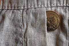 Thai coin with a denomination of 5 baht in the pocket of worn linen pants. Thai coin with a denomination of five baht in the pocket of worn flax pants Royalty Free Stock Photos