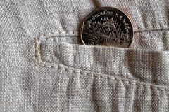 Thai coin with a denomination of five baht in the pocket of worn linen pants. Thai coin with a denomination of 5 baht in the pocket of worn flax pants Royalty Free Stock Photos