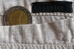 Thai coin with a denomination of 10 baht in the pocket of linen pants with black stripe for label. Thai coin with a denomination of ten baht in the pocket of Royalty Free Stock Photos