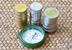 Thai coins and a compass on wooden table Royalty Free Stock Photo