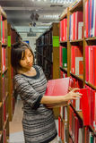 Thai college girl is selecting book from the shelf Stock Images