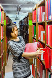Thai college girl is selecting book from the shelf Stock Photography