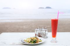Thai cuisine, fried noodles. And watermelon fruit shake in beach cafe or restaurant stock photos