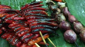 Thai cuisine, grilled spicies. Red peppers, purple onions with banana leaf stock video footage