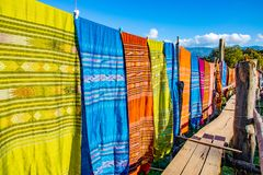 Thai cultural cotton fabric hanging along wooden bridge royalty free stock photography