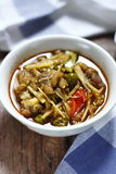 Thai curry of pork leg with mixed vegetables. In a small bowl on wooden table Stock Photos