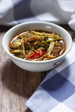 Thai curry of pork leg with mixed vegetables. In a small bowl on wooden table Royalty Free Stock Photo
