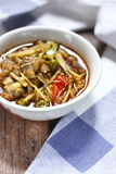 Thai curry of pork leg with mixed vegetables. In a small bowl on wooden table Royalty Free Stock Images