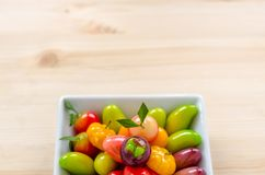 Thai dessert: delectable imitation fruits on the wooden background.  stock photo