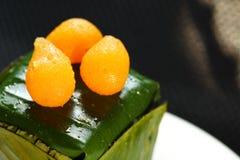 Thai dessert egg yoke fudge balls on banana leaf scene. stock photography