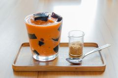 Thai dessert. Grass Jelly in thai tea with brown sugar Royalty Free Stock Image
