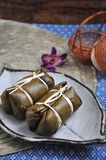 Thai Dessert Sticky Rice filled with Banana put on Plate. Thai dessert sticky rice filled with banana wrapped with banana leaf put on white plate royalty free stock image
