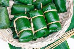 Thai dessert sticky rice steamed in banana leaf ( Khao Tom Mat ). In rattan tray Stock Image