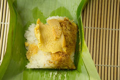 Thai dessert, Sticky rice with steamed custard, wrapped in banan. A leaf royalty free stock photo