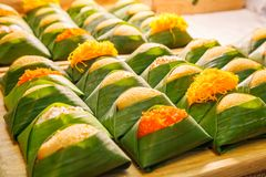 Free Thai Dessert: Sweet Sticky Rice With Steamed Egg Custard With Topping Varieties Wrapped With Banana Leaves Package Displayed Stock Image - 111255571