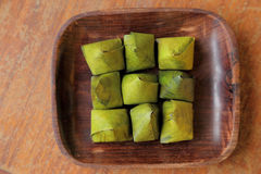 Thai dessert wrapped in banana leaves on wooden dish Royalty Free Stock Photography