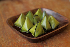 Thai dessert wrapped in banana leaves on wooden dish Royalty Free Stock Photo
