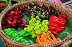 Thai desserts Deletable Imitation Fruits (Kanom Look Choup). A ball of cloth with a Thai sweets made with a mold shape green beans mill to mix paints, and take royalty free stock photography