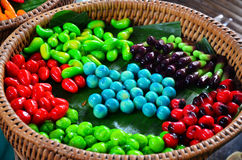 Thai desserts Deletable Imitation Fruits (Kanom Look Choup). A ball of cloth with a Thai sweets made with a mold shape green beans mill to mix paints, and take stock photo