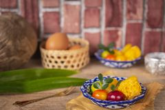 Thai desserts on a plate of white and blue stripes placed on golden cloth and wood table there are Similar object, pandan, water. Bowl, egg in basket and stock image