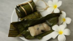 Thai Desserts, Porridge tie, Sticky rice wrapped in banana leaves, Banana filling, Steamed cooked food. On white disk and white flowers stock video footage