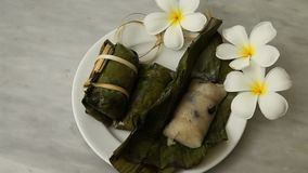 Thai Desserts, Porridge tie, Sticky rice wrapped in banana leaves, Banana filling, Steamed cooked food. On white disk and white flowers stock video