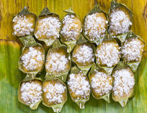 Thai desserts wrapped in banana leaves. Thai dessert of fruit juice mixed with flour, sprinkle with coconut wrapped in banana leaves and steamed until cooked to Royalty Free Stock Images