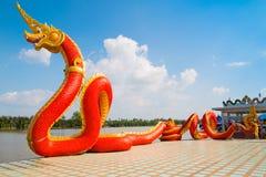 Thai dragon or Naga statue with blue sky background Stock Photo